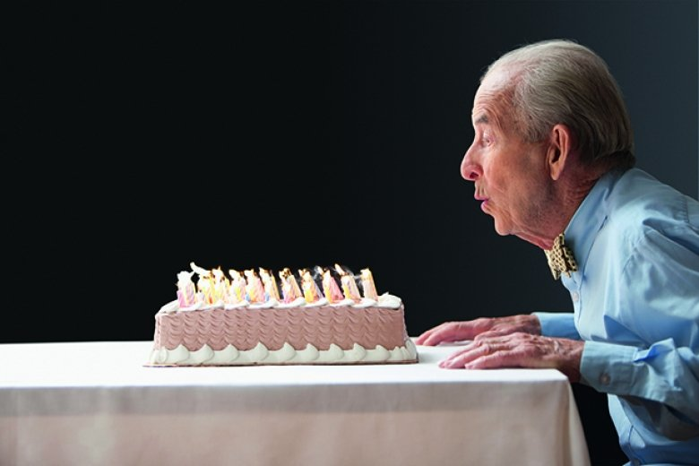 Old man blowing out birthday candles