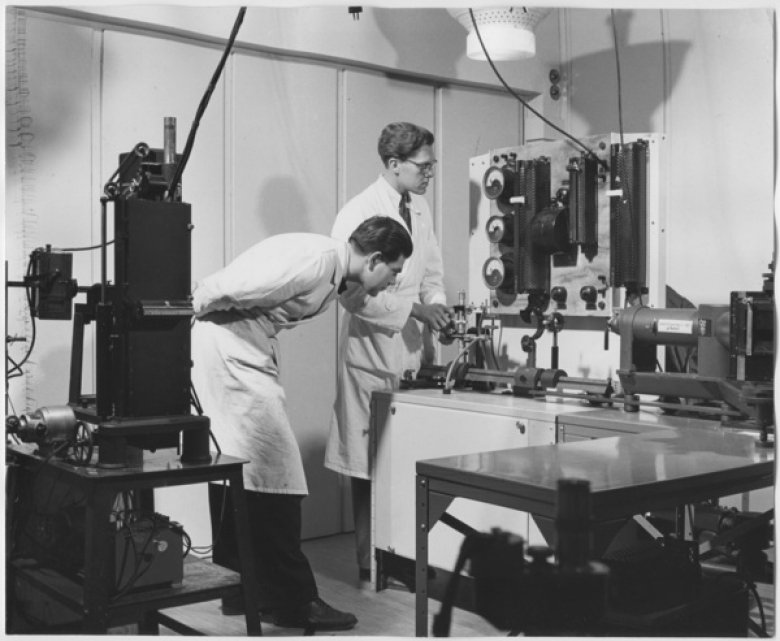 Men in lab coats by large measuring device.