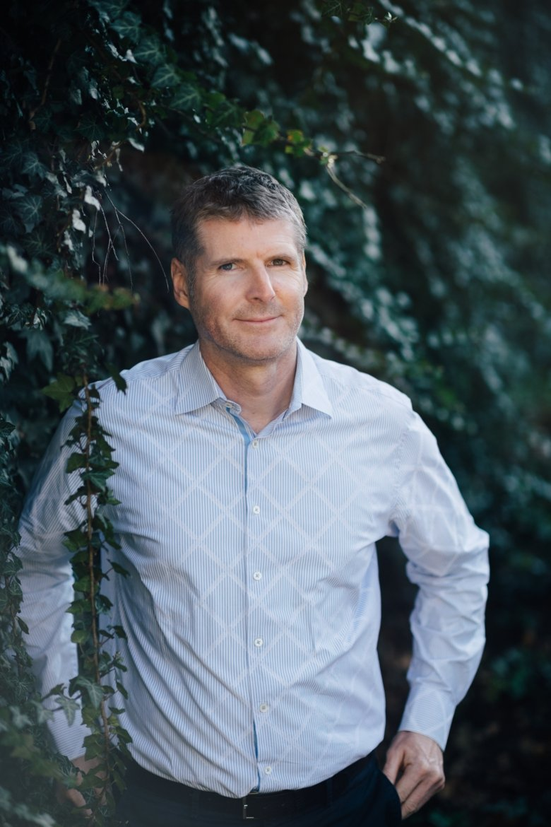 Portrait of Peder Olofsson in front of green bushes and dressed in a light-blue shirt.