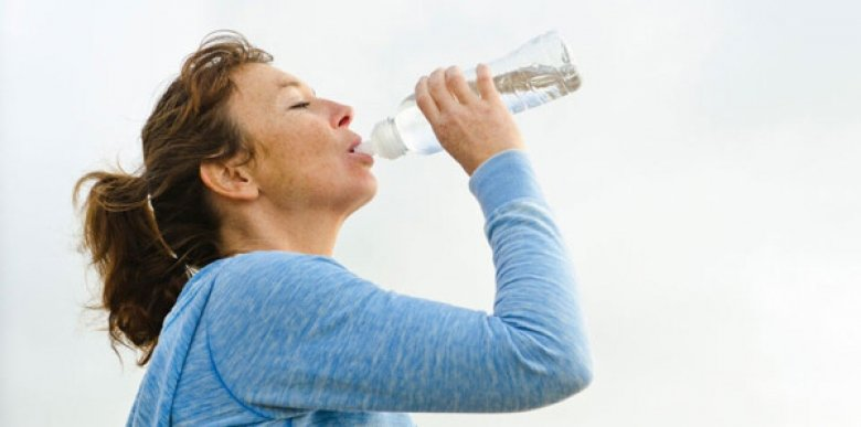 Woman drinking water, genre image.